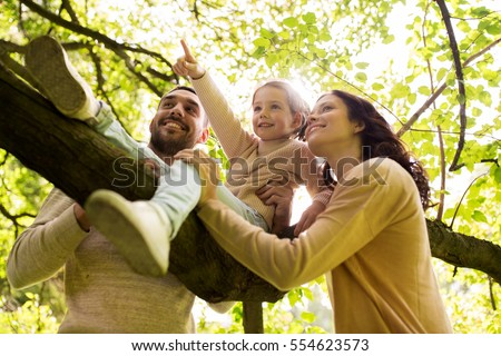 family, parenthood, adoption and people concept - happy mother, father and little girl in summer park having fun #554623573