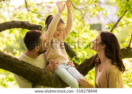 family, parenthood, adoption and people concept - happy mother, father and little girl in summer park having fun #558278848