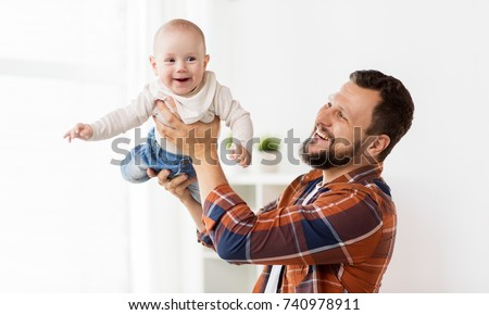 family, parenthood and people concept - happy father playing with little baby boy at home
