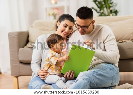 family, parenthood and people concept - happy mother, father and baby daugter reading book at home
