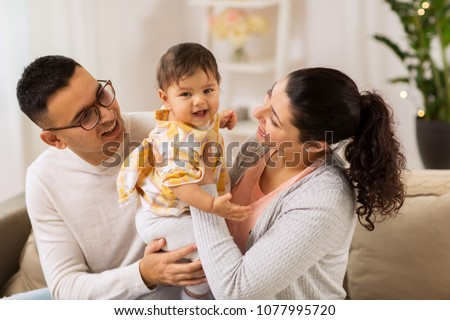 family, parenthood and people concept - happy mother, father with baby daughter at home Foto stock ©