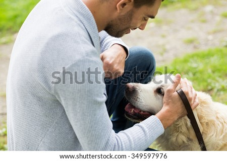family, pet, animal and people concept - close up of happy man with labrador retriever dog on walk
