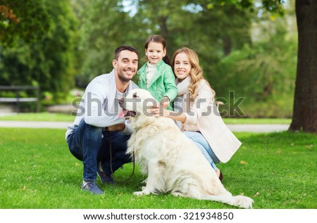 family, pet, domestic animal and people concept - happy family with labrador retriever dog on walk in summer park
