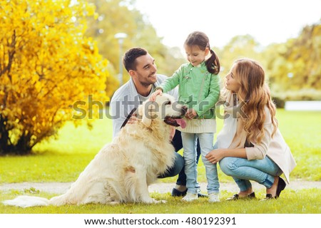 family, pet, domestic animal and people concept - happy family with labrador retriever dog on walk in autumn city park