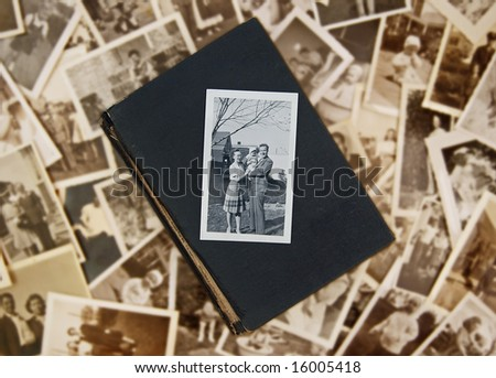 Family photo atop old book on pile of vintage photos