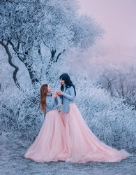 Family photo happy mom daughter look each other love smile face. Cup tea hands. Luxury long puffy gown costume same set warm sweater scarf. Winter fabulous nature tree covered hoarfrost snow ice frost