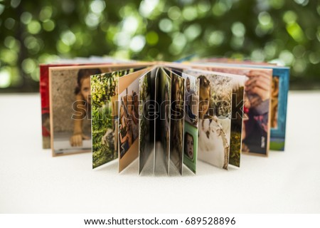 Family photos archive saved in brightly designed photo book; bright summer memories placed in the photobook