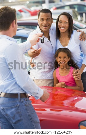 Family picking up new car from salesman
