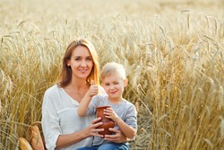 family picnic in nature on a family picnic in nature on a summer evening. mother and son eat bread, drink milk from a ceramic jug in a wheat field
