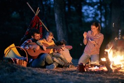 Family picnic in the woods with fire; Spring or autumn camping with campfire at night ; camping, travel, tourism, hike and people concept. Quality family time together.