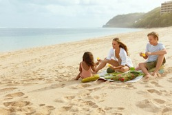 Family Picnic On Beach. Portrait Of Happy Mother, Son And Daughter Having Lunch On Sandy Coast. Young Woman With Cute Little Girl And Handsome Boy Eating Food And Enjoying Summer Vacation.