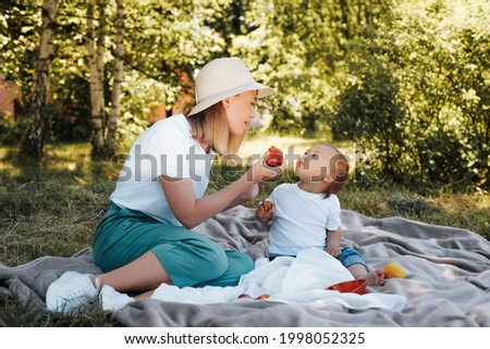 Family picnic outdoors. Beautiful young mother in a hat nursing her adorable child while sitting on a blanket in nature. Son funny looking at mom who gives him fruit. Family having fun in the summer. Foto stock ©