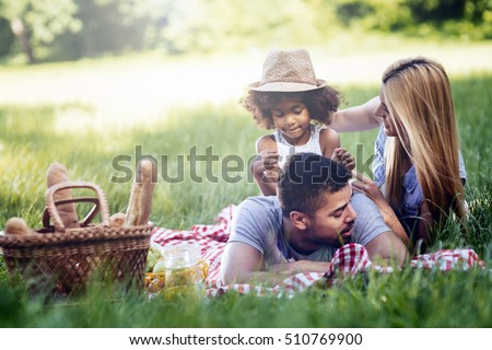 Family picnicking outdoors with their cute daughter