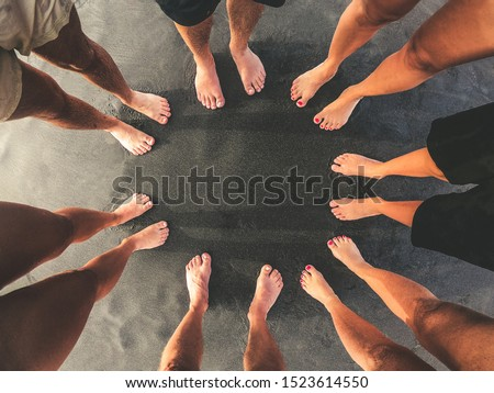 Family picture, all feet together on a beach with black sand. Top view of a group of people standing in a circle barefoot. Mother, father and sons enjoying summer holiday. Togetherness, unity concept