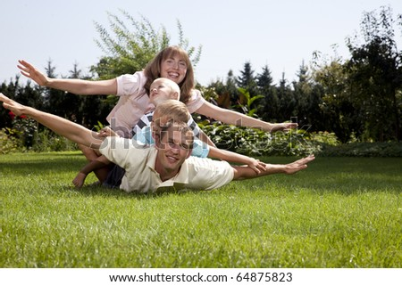 Family playing airplane on grass