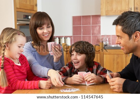 Family Playing Cards In Kitchen