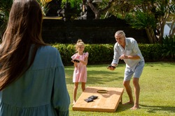Family playing cornhole game outdoor on sunny summer day. Parents and children playing bean bag toss
