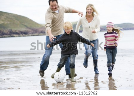 Family playing football on beach
