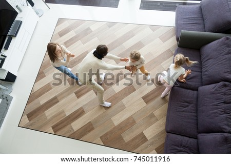 Family playing hide and seek game at home, mother and kids hiding clapping hands while blindfolded father seeking catching children wife, parents and son daughter having fun in living room, top view