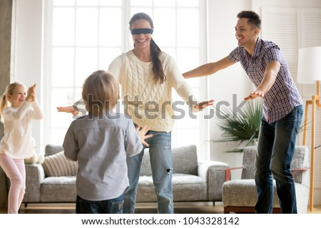 Family playing hide and seek game together with blindfolded mother, happy kids and parents having fun in living room, children hiding clapping hands enjoying interesting activity with mom dad at home