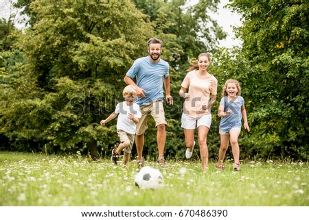 Family playing soccer in summer with their children