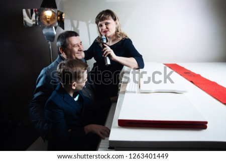 Family playing the piano and singing songs into the microphone #1263401449