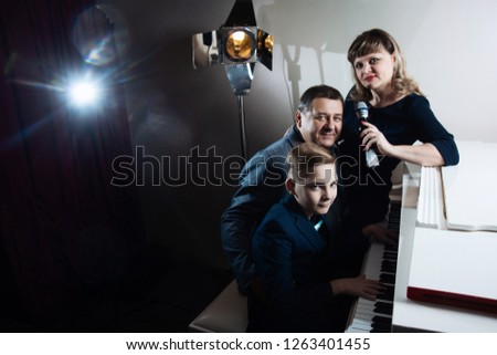 Family playing the piano and singing songs into the microphone #1263401455