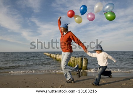 Family playing with balloons on the beach
