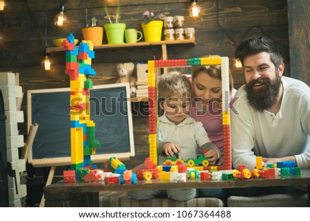 Family playing with constructor at home. Father, mother and son play near big frame construction made out of toy bricks, plastic blocks. Mother and cute son play with constructor. Family time concept. #1067364488