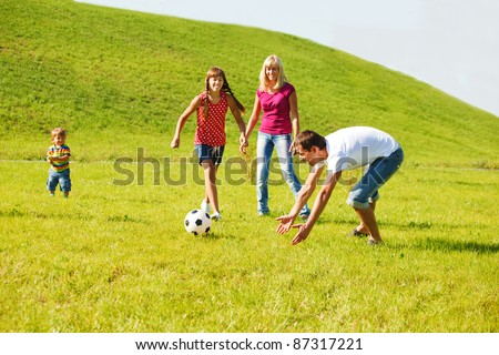 Family playing with the ball in summer park