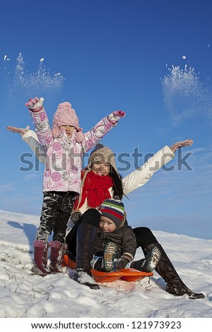family playing with the snow during the holidays