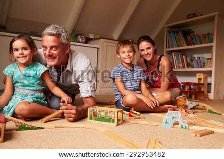 Family playing with toys in an attic playroom, portrait