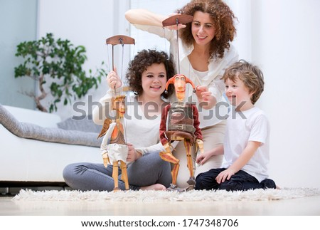 Family playing with wooden puppets on rug in living room