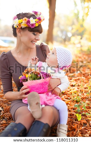 Family portrait cute little girl and cheerful mom. Posing in a park on a background of autumn leave. Series of photos in my portfolio