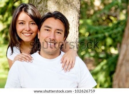 Family portrait of a brother and sister smiling outdoors