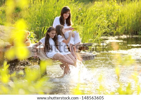 Family portrait of a smiling and cheerful mother and two daughters on a picnic at the lake