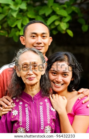 family portrait of asian ethnic elderly woman with young adult son and daughter