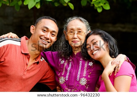 family portrait of asian ethnic senior woman with young adult son and daughter