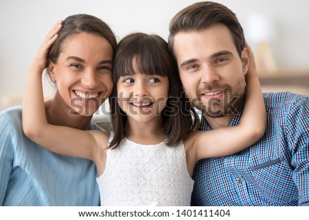 Family portrait of cute little daughter stand in between smiling young parents hugging them, happy mom and dad posing together with small girl child looking at camera laughing and cuddling #1401411404