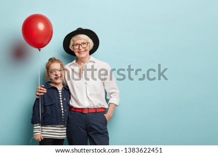 Family portrait of dranddaughter and granny embrace and celebrate holiday, hold air ballonon, wear festive clothes, express positive emotions isolated on blue studio wall. Generation and fest concept