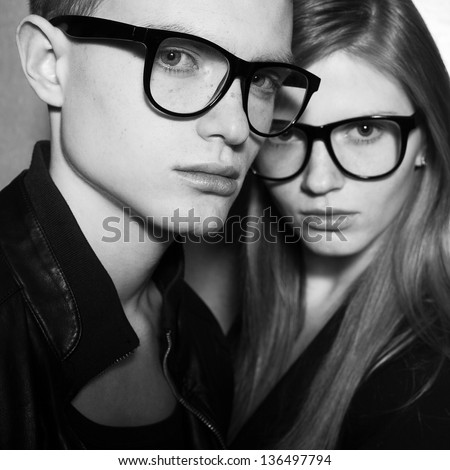 Family portrait of gorgeous blond fashion twins in black clothes wearing trendy glasses and posing over gray background together. Perfect hair. Natural make-up. Perfect skin. Vogue style. Close up. - stock photo