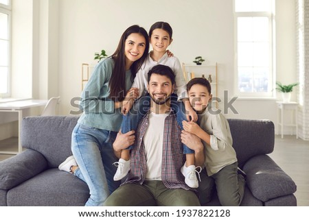 Family portrait of happy loving young parents with little daughter and son at home on sofa. Friendly family has fun on the weekends at home and poses in front of the camera. Love and family concept.