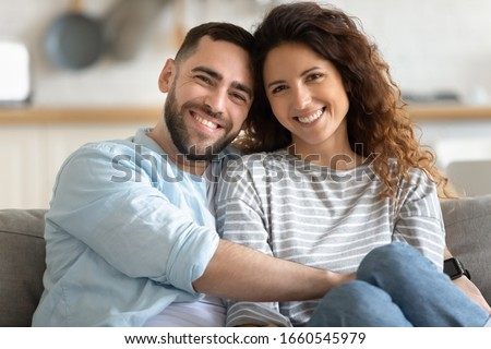 Family portrait of happy millennial husband and wife sit on couch hug cuddle look at camera posing, smiling young couple embrace show love affection, relax at home on weekend together