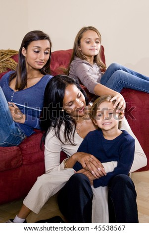Family portrait of Indian mother with 3 mixed-race children sitting at home together on sofa