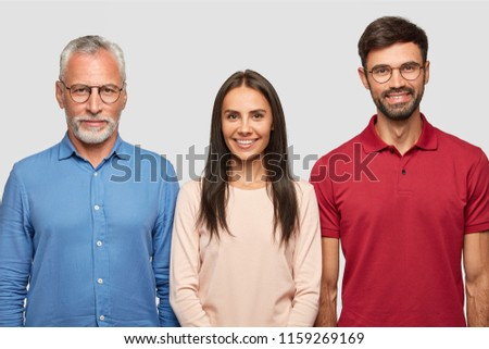 Family portrait of mature grey haired male and his attractive son, daughter, stand closely, pose for album photos, have cheerful expressions, have good relationships. People, age and family concept