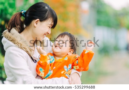 family portrait of 2 years old baby feeling happy and smiles with her mother in the garden.