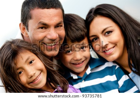 Family portrait outdoors looking happy and smiling - stock photo