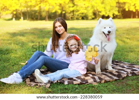 Family portrait, pretty young mother and child walks with dog outdoors in the park