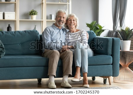 Family portrait smiling mature couple sitting on couch in cozy living room, happy wife and husband hugging, looking at camera, aged man and woman posing for photo in modern apartment