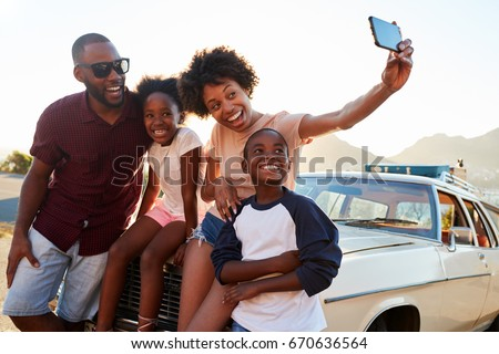 Family Posing For Selfie Next To Car Packed For Road Trip #670636564